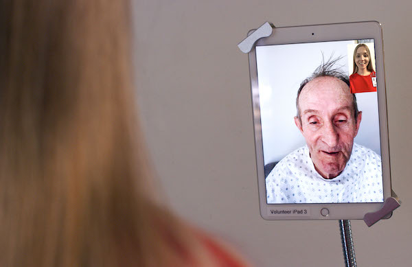 HELP volunteers use iPads to connect virtually to hospitalized older adult patients at University of Utah Hospital.